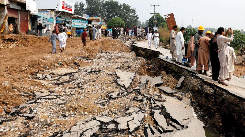 الأهالي يقفون بجوار أحد الطرق التي دمرها الزلزال. رويترز