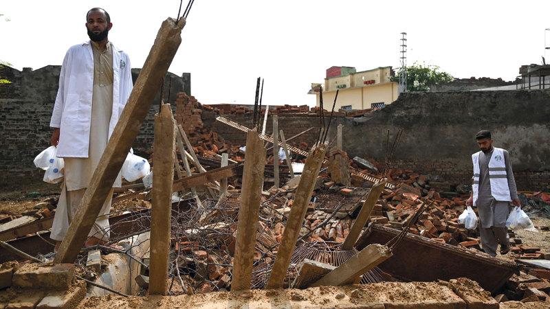 متطوع يحمل زجاجات مياه للناجين من الزلزال. أ.ف.ب