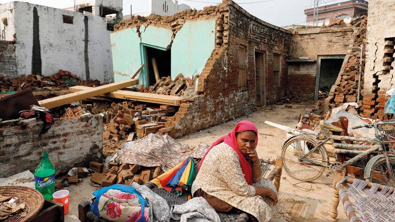 امرأة تجلس وسط حطام منزلها. رويترز