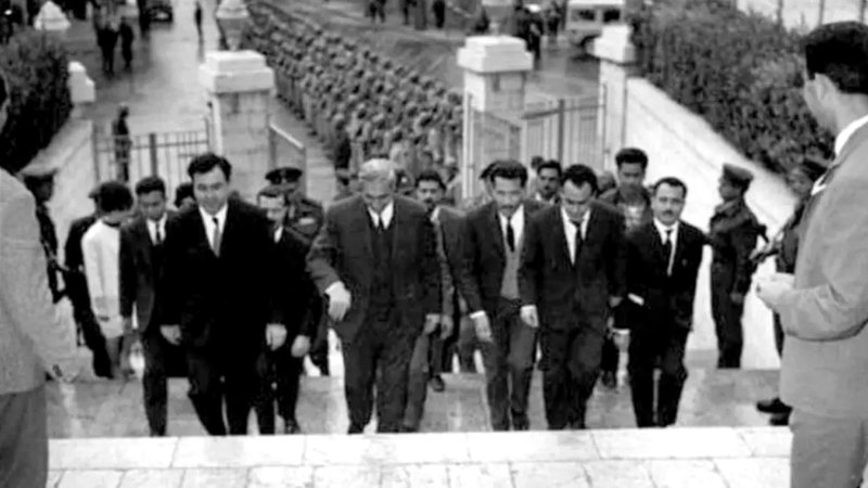كوهين في حاشية الرئيس السوري أمين الحافظ إلى جانب وزير الداخلية نور الدين الفطاسي عام 1964. أرشيفية