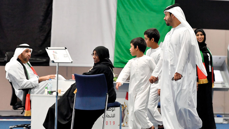 مواطنون حضروا برفقة أطفالهم للإدلاء بأصواتهم في أحد المراكز الانتخابية بأبوظبي. تصوير: نجيب محمد