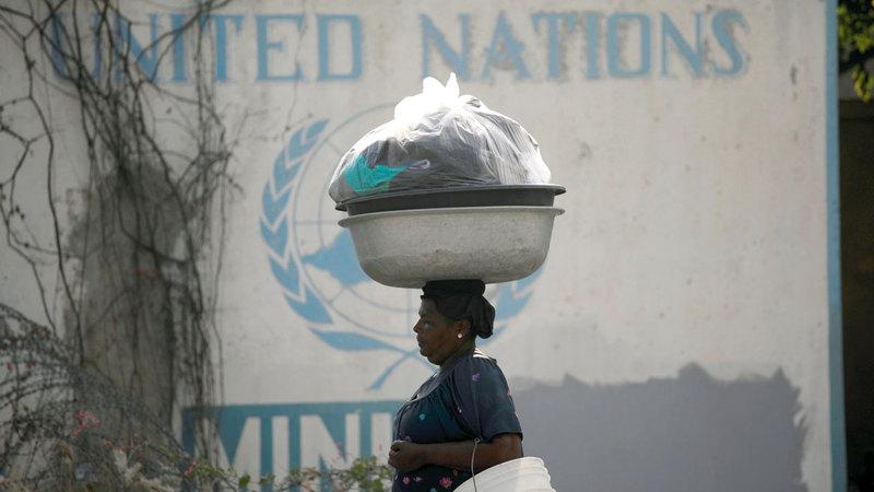 سيدة تحمل أغراضاً لبيعها تمرّ قبالة مقر البعثة الأممية في بورت أو برنس. رويترز