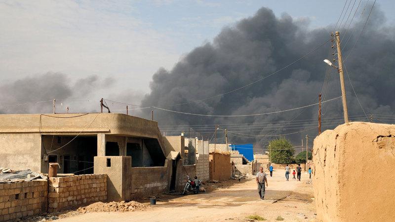 الدخان يتصاعد نتيجة الاشتباكات بين القوات التركية وقوات سورية الديمقراطية بالقرب  من مدينة رأس العين الحدودية. إي.بي.إيه