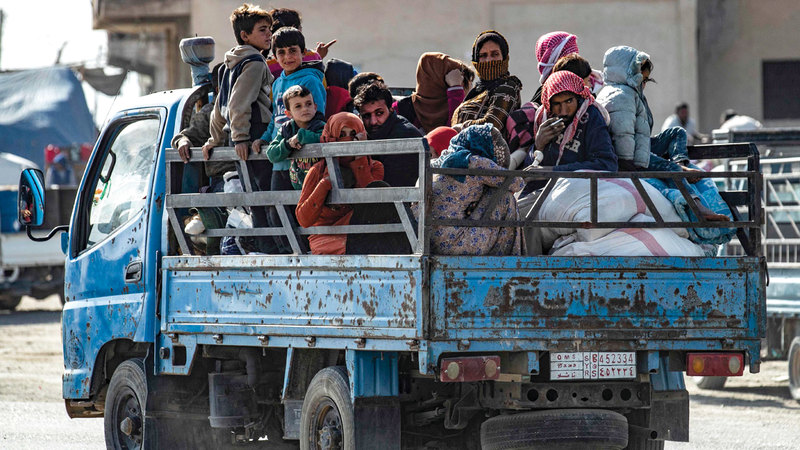 عائلة سورية ضمن الآلاف ممن رحلوا جراء العدوان التركي. أ.ف.ب