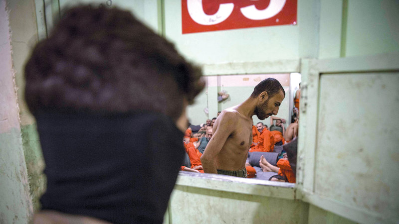 أحد أفراد «قوات سورية الديمقراطية» يحرس السجناء. أ.ف.ب