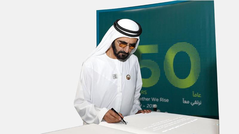 محمد بن راشد وقّع على اللوحة الإلكترونية التذكارية للبنك. وام