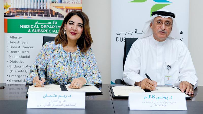 كاظم (يمين) وعثمان خلال توقيع الاتفاقية مع المستشفى السعودي الألماني. من المصدر