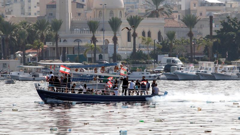 متظاهرون يلوحون بالأعلام اللبنانية على متن قارب بمدينة طرابلس الساحلية أمس. أ.ف.ب