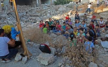 """الصورة: جعل الأطفال يفرحون.. """"وليد"""" ينشر السعادة وسط دمار أدلب"""
