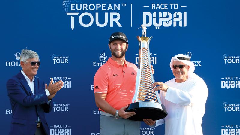 جون رام تسلّم كأس «السباق إلى دبي» من يوسف كاظم. من المصدر