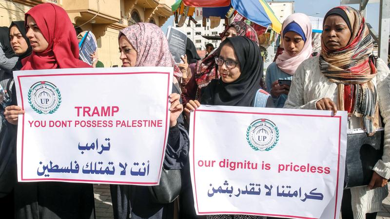 فلسطينيات يحملن لافتات ضد الاستيطان في غزة أمس. أ.ف.ب