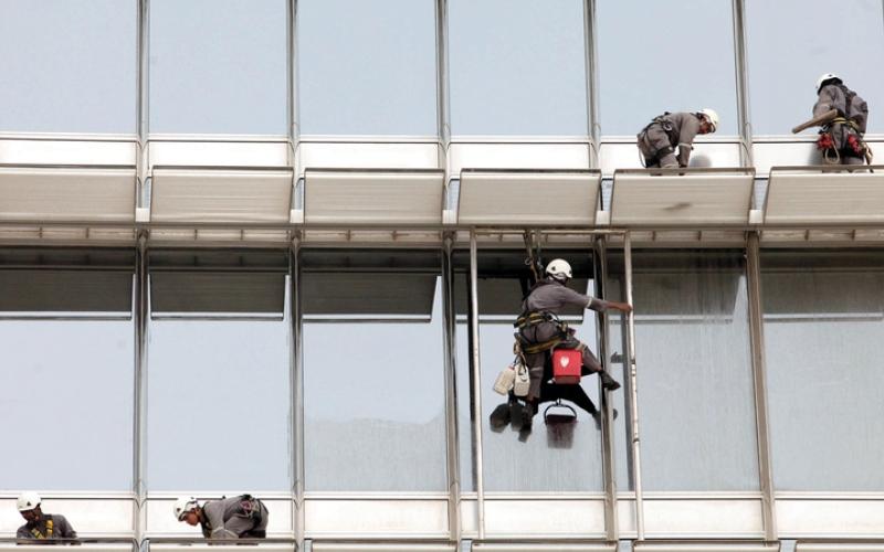 الصورة: اشتراطات لحماية عمال تنظيف واجهات المباني من السقوط