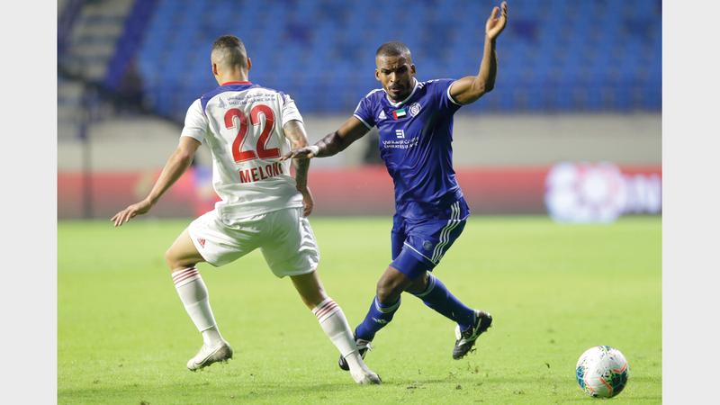 محمود خميس (يمين) يحاول المرور من لاعب الشارقة ميلوني. تصوير: مصطفى قاسمي