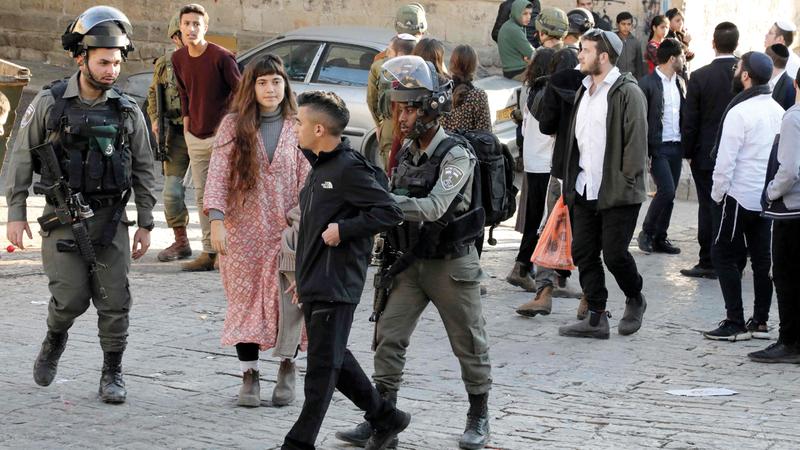 جندي إسرائيلي يدفع شاباً فلسطينياً بعيداً عن مجموعة مستوطنين في الخليل.  أ.ف.ب