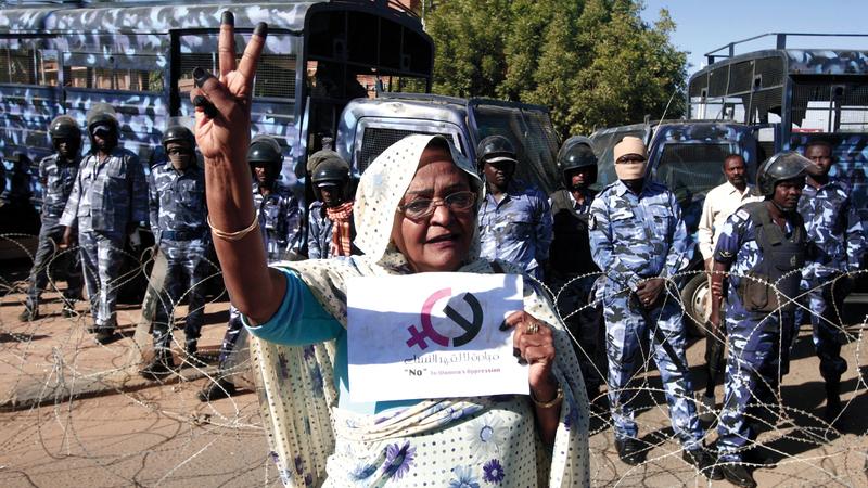 سيدة سودانية تحتج في أم درمان أمام حشد من رجال الشرطة. أ.ف.ب