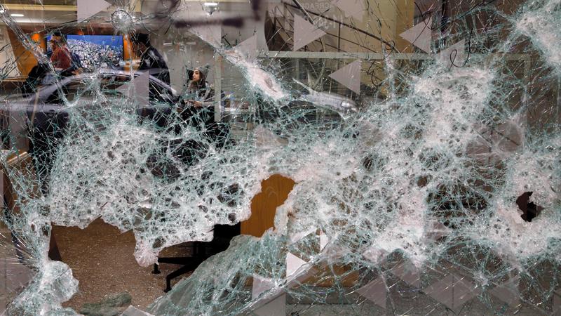 لبنانيون داخل بنك تحطمت واجهته. أ.ب