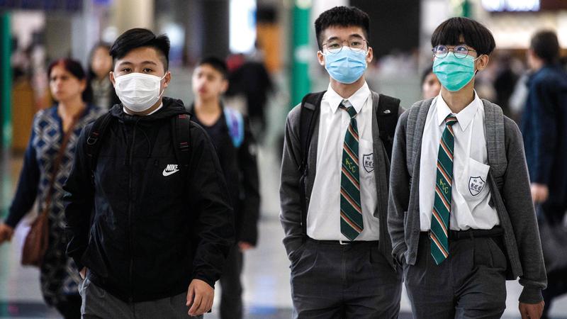 طلاب يضعون الأقنعة في مطار هونغ كونغ الدولي.  أ.ف.ب