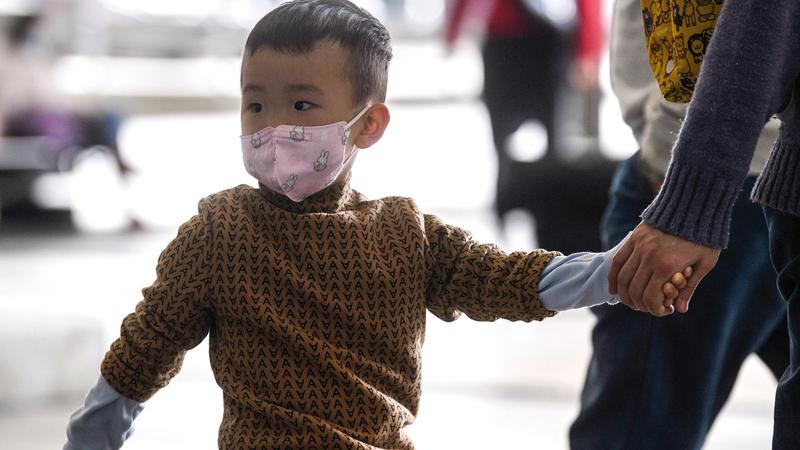 طفل يضع قناعاً واقياً وهو ممسك بيد أبيه في مطار هونغ كونغ.  أ.ف.ب