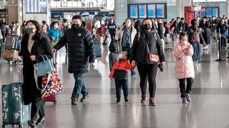 مسافرون يضعون الأقنعة الواقية في مطار بكين. أ.ف.ب