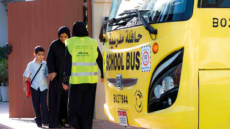 المشرفة تساعد الطالب في صعود الحافلة بهدوء ونظام.  من المصدر