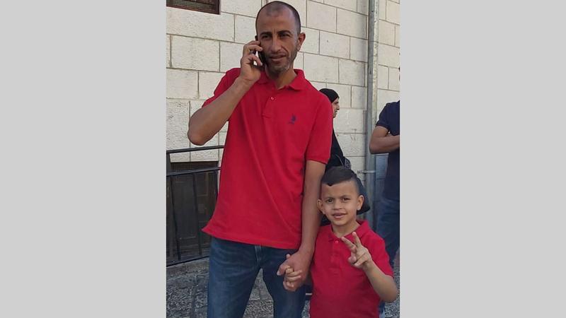 الطفل محمد عليان ووالده أثناء توجههما إلى مركز التحقيق في الشرطة الإسرائيلية. من المصدر