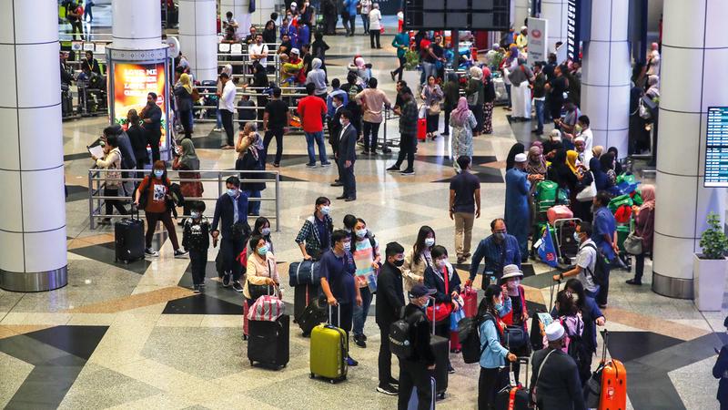 سياح بمطار كوالامبور بماليزيا يرتدون الكمامات خشية الإصابة بفيروس كورونا. إي.بي.إيه