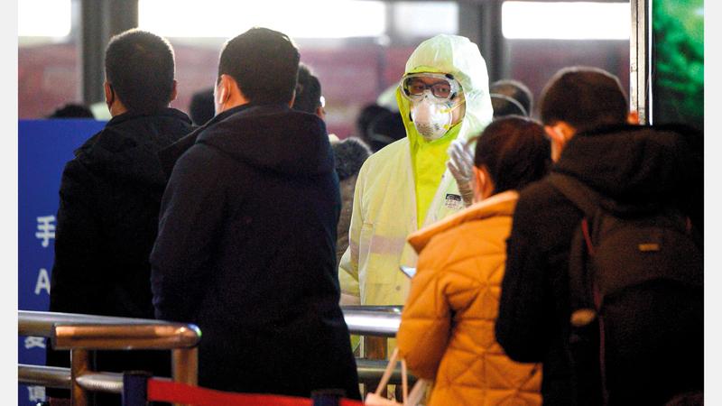 ممرّض يفحص المسافرين في محطة قطار شنغهاي. أ.ف.ب