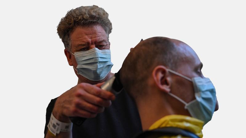 أثر الفيروس يمتد في كل القطاعات حيث يبدو حلاق فرنسي وهو يقص شعر زبون في منتجع بالقرب من مرسيليا الفرنسية.  أ.ف.ب