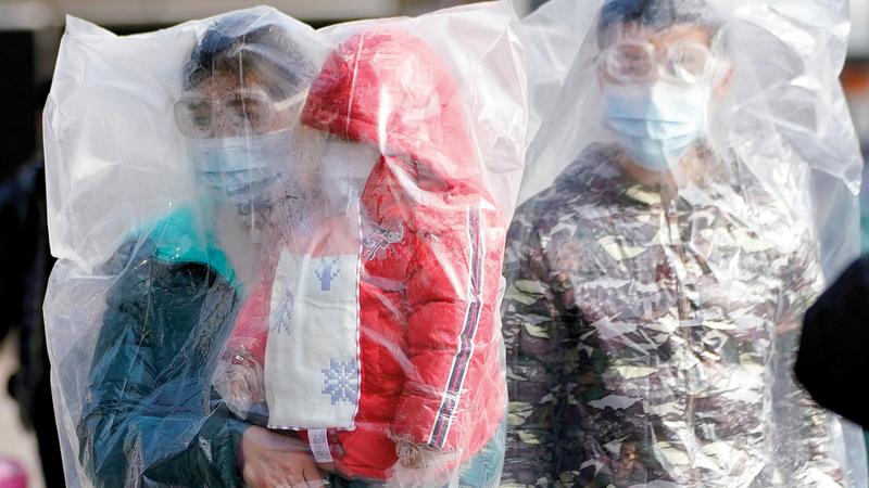 مسافرون يرتدون أقنعة واقية ويتدثرون بأكياس البلاستيك يخرجون من محطة قطار شنغهاي في الصين. رويترز