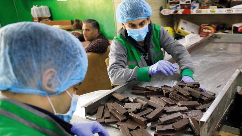عاملان يعبئان البسكويت المغطى بالشوكولاتة في مصنع العريس. À ا.ف.ب