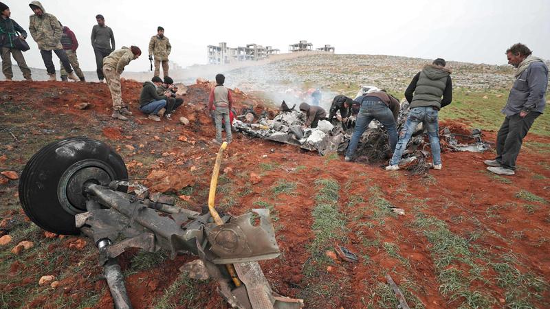 سوريون في موقع المروحية الحكومية التي تم إسقاطها في ريف حلب الغربي. أ.ف.ب
