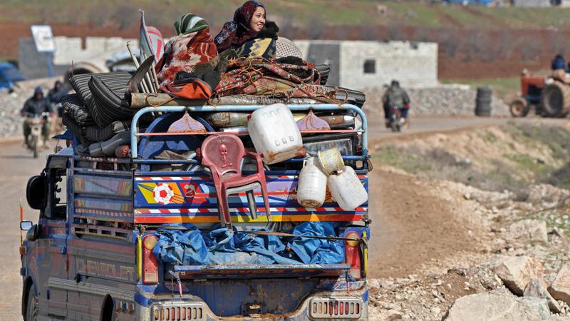 شاحنة تقل نازحين سوريين تمر بجوار دير بلوط في طريقها إلى عفرين وعزاز بالقرب من الحدود التركية.    ■ أ.ف.ب