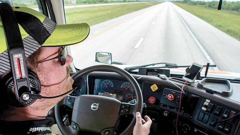 أحد سائقي الشاحنات الذاتية الحركة داخل قمرة القيادة.  من المصدر