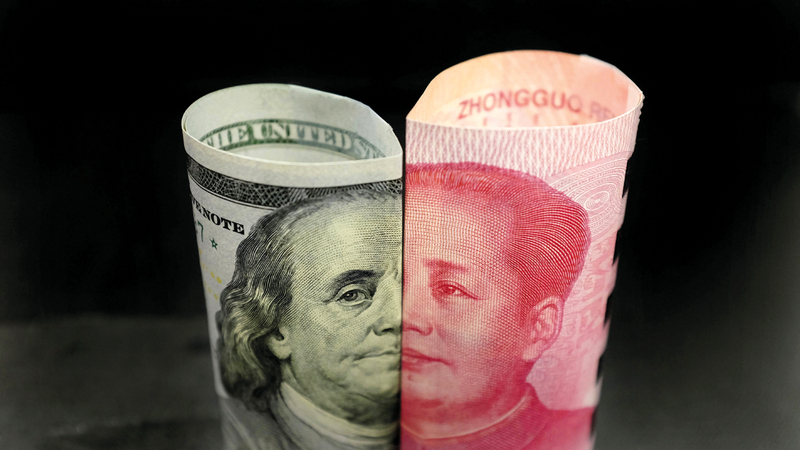 عملة أميركية وصينية تحمل صورتي الزعيمين: الأميركي بنيامين فرانكلين، والصيني ماو سيتونغ. رويترز
