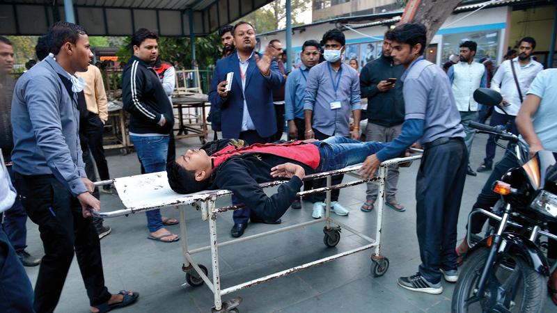 رجال الإنقاذ ينقلون أحد المصابين في الصدامات.  إي.بي.أيه