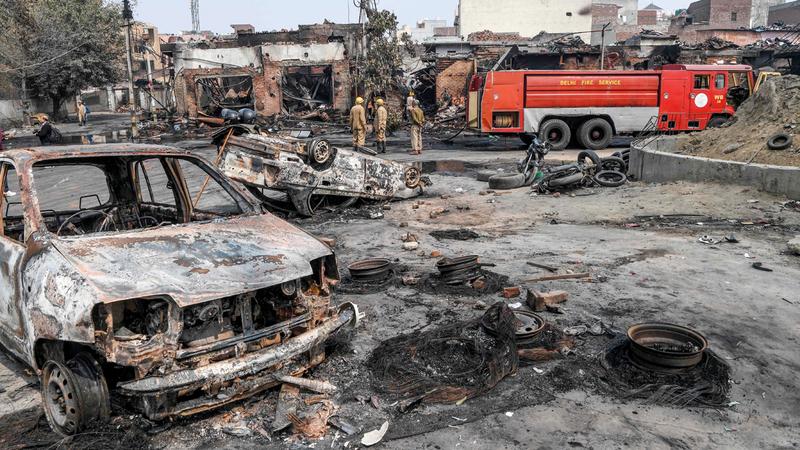 رجال الإطفاء يقفون وسط سوق للإطارات أحرقت بالكامل.  أ.ف.ب