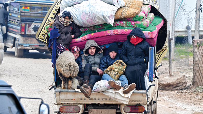 أسرة سورية من إدلب تتجه إلى الحدود التركية.  أ.ف.ب