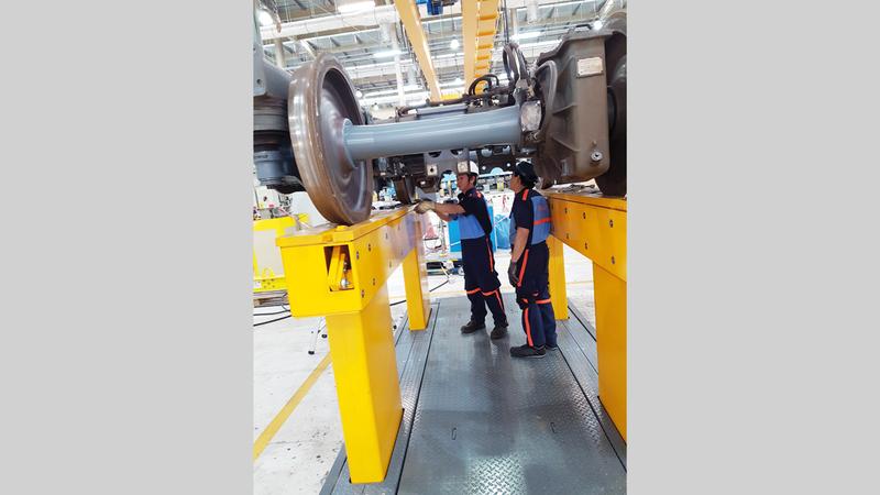 فنيان يتابعان العمل داخل ورشة صيانة قطارات المترو في القصيص. الإمارات اليوم