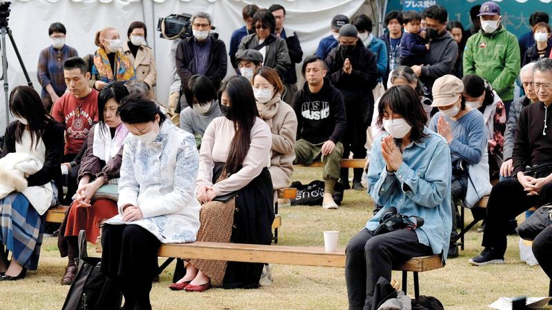 يابانيون يقفون دقيقة صمتاً إحياء لذكرى الضحايا.   أ.ف.ب
