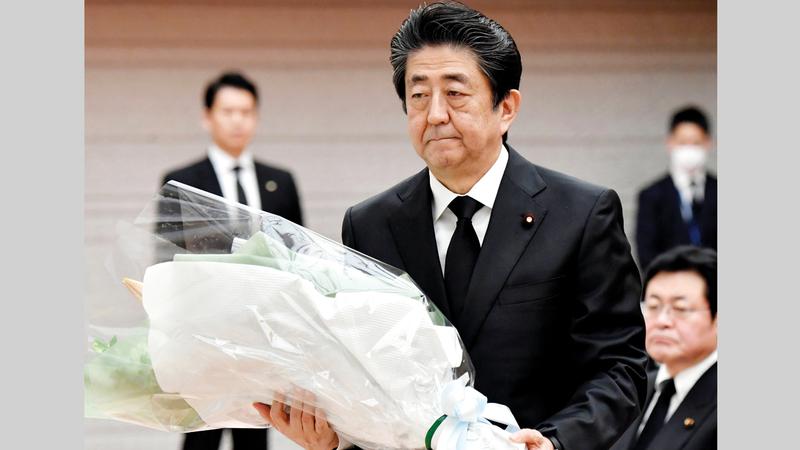 شينزو آبي يضع باقة زهور على نصب شكلي لضحايا تسونامي في مكتبه أمس.   أ.ب