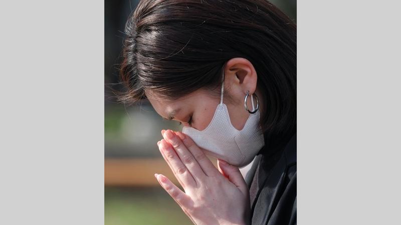 سيدة يابانية تقف دقيقة صمتاً إحياء لذكرى ضحايا الزلزال وتسونامي.   أ.ف.ب
