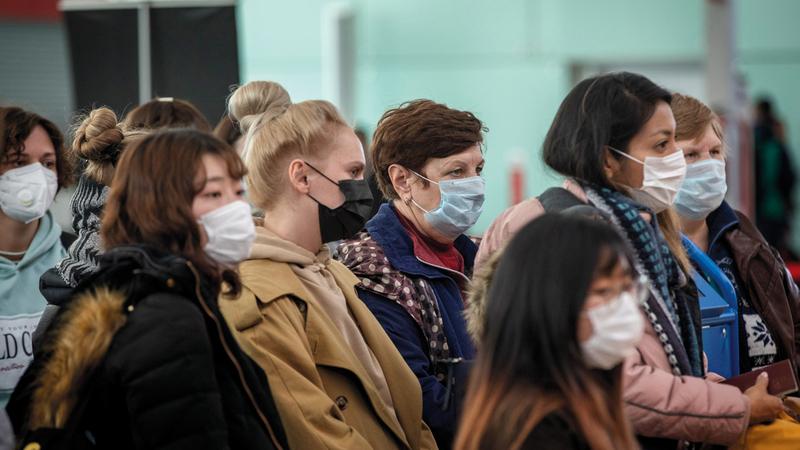 مسافرون يرتدون الأقنعة أثناء انتظارهم لتسجيل الوصول في مطار برشلونة بإسبانيا.  أ.ب
