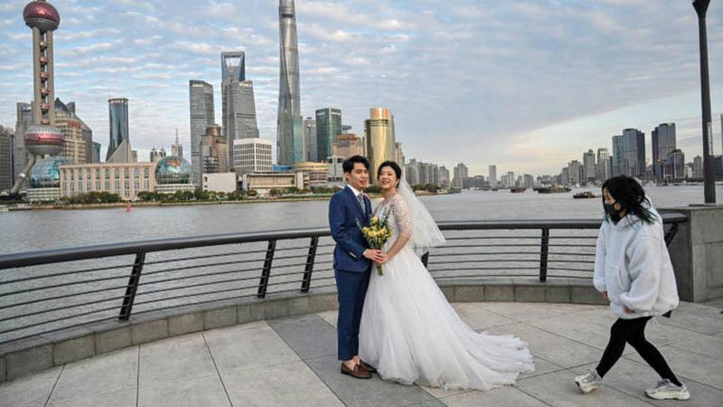 عروسان يلتقطان الصور بعيداً عن جمهور المدعوين.  أ.ف.ب