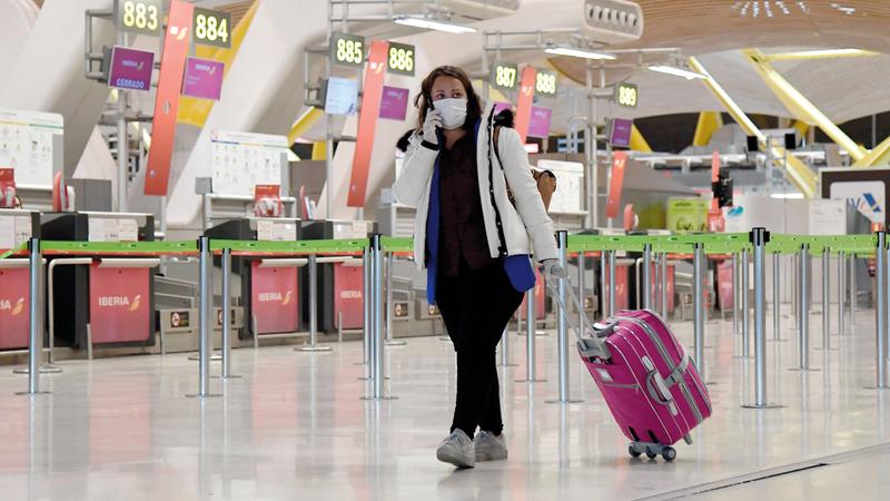مسافرة تسحب حقيبتها في مطار مدريد - باراخاس.  أ.ف.ب