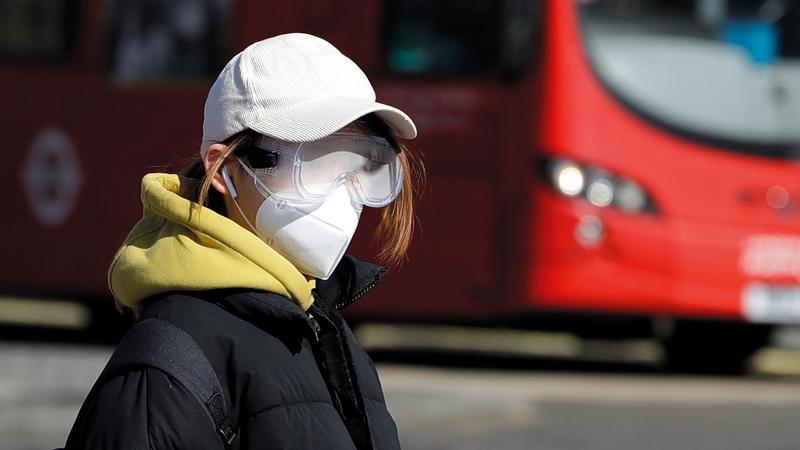 فتاة بريطانية ترتدي قناعاً ونظارة واقيين في لندن أمس.  أ.ب