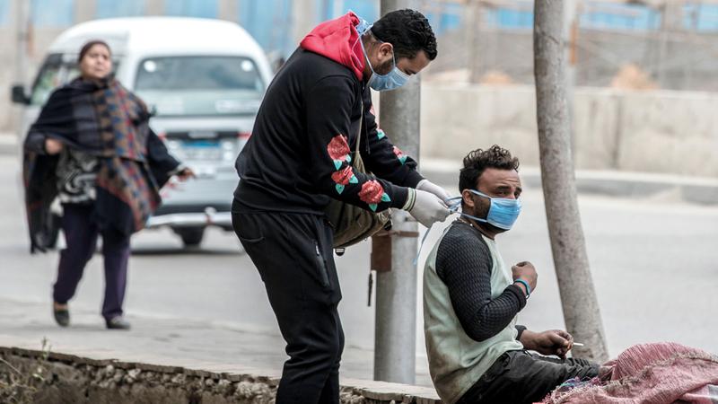متطوع يوزع كمامات في شوارع القاهرة. أ.ف.ب