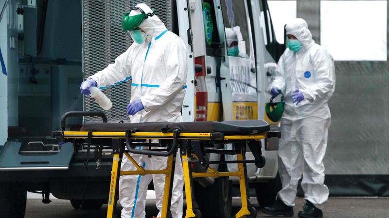 مسعفان يقومان بتطهير نقالة خارج مستشفى بورغوس في شمال إسبانيا.  أ.ف.ب