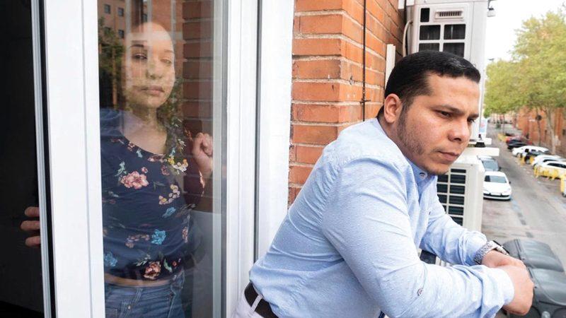 الممرضة موي والطبيب أليخاندرو في شقتهما، لأنهما لا يستطيعان ممارسة مهنتهما في إسبانيا.