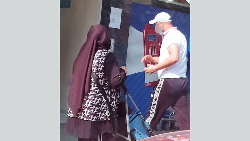 متسولة تحاول استعطاف أحد المستهلكين أمام مركز تجاري. الإمارات اليوم
