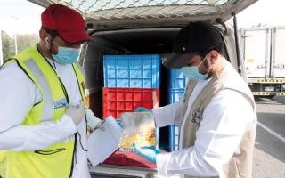 """الصورة: """"الإمارات اليوم"""" تشارك في توزيع 50 ألف وجبة إفطار على العمال"""